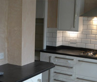 Kitchen fitting with white gloss cabinets and a dark top finish