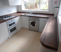 Kitchen fitting with cream gloss cabinets and a light wood top finish