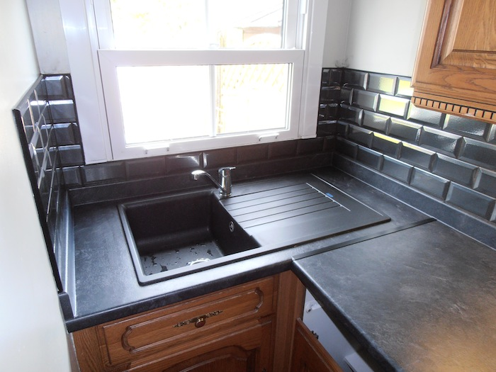 Kitchen fitting with black tiles with dark kitchen top