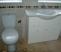 Bathroom fitting with white cabinets and white and coloured tiles